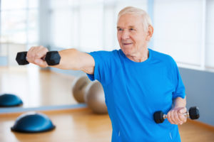 Confident senior man exercising with dumbbells and smiling while standing in health club