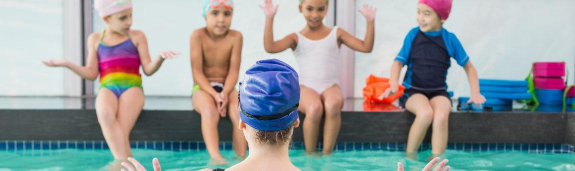 swim instructor teaching class of kids