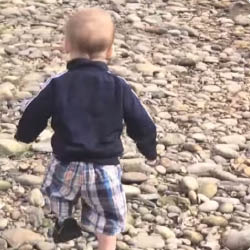 toddler boy walking across rocks